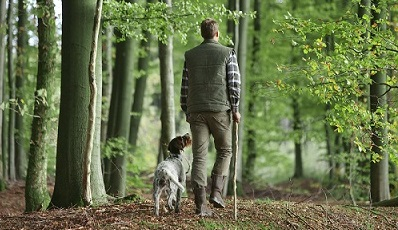 Man-Walking-with-Dog-in-Woods-400-x-266